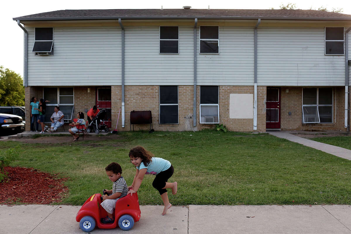 Aden Garcia, 2, is pushed by Ruth Castillo, 4, outside their apartment at the Village East Apartments in San Antonio on Tuesday, July 8, 2014. The family moved to Village East Apartments from the original Sutton Homes apartments when the renovation began. They are waiting for the construction of the four bedroom apartments to be complete to move to the new Sutton Oaks complex.