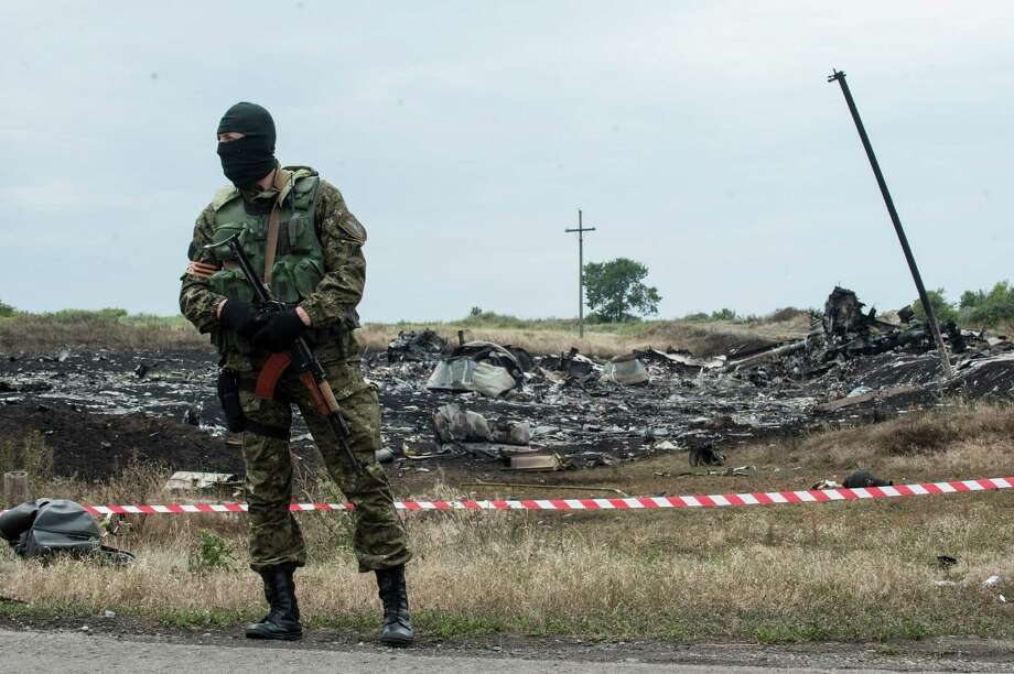 FILE - This July 19, 2014, file photo shows  pro-Russian fighter guarding the crash site of Malaysia Airlines Flight 17 near the village of Hrabove, eastern Ukraine. Ukraine said the passenger plane was shot down as it flew over the country, killing all 298 people on board. A series of unanswered questions about the downing of the flight shows the limits of U.S. intelligence-gathering even when it is intensely focused, as it has been in Ukraine since Russia seized Crimea in March. (AP Photo/Evgeniy Maloletka, File) Photo: Evgeniy Maloletka, STR / AP