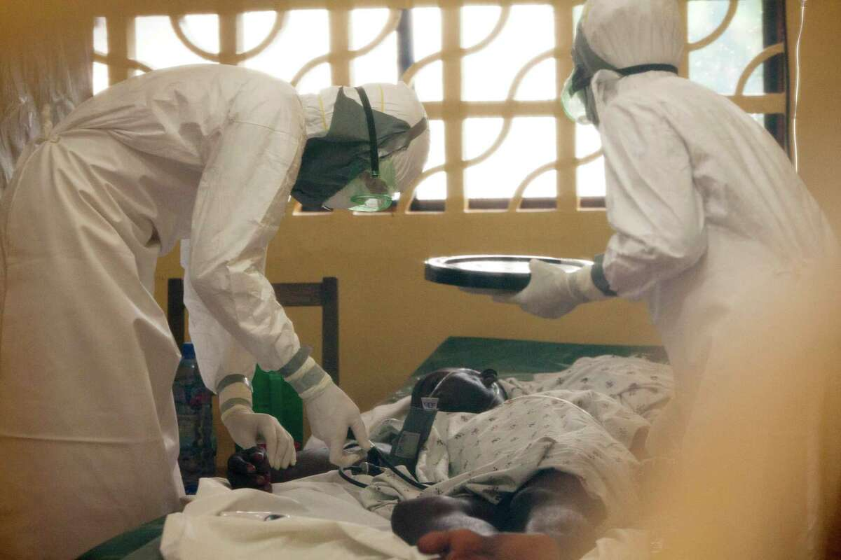 In this 2014 photo provided by the charity Samaritan's Purse, Dr. Kent Brantly, left, treats an Ebola patient at the aid group's Ebola center in Monrovia, Liberia.