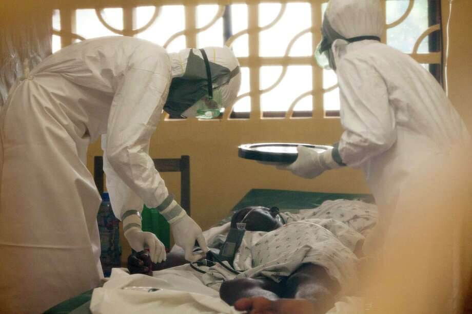 In this 2014 photo provided by the charity Samaritan's Purse, Dr. Kent Brantly, left, treats an Ebola patient at the aid group's Ebola center in Monrovia, Liberia. Photo: HONS / Samaritan's Purse