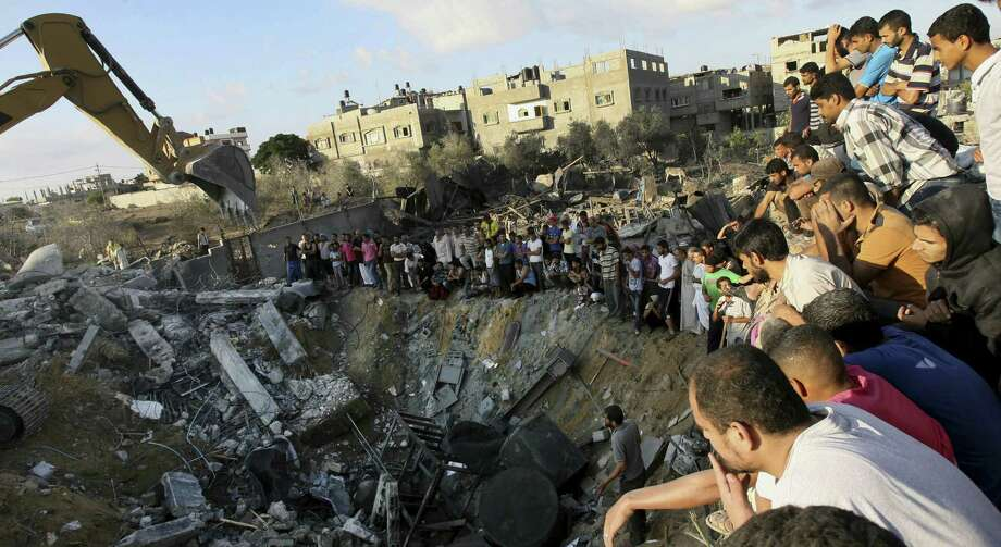 Palestinians gather around the rubble of a building where at least 20 members of the Al Najar extended family were killed by an Israeli strike in Khan Younis, in the southern Gaza Strip. Photo: Associated Press / AP