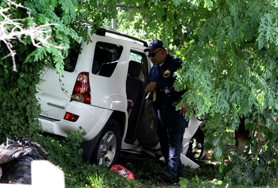 Investigators gather evidence  at the scene of a fatal accident in North Philadelphia on Friday. Three young siblings were killed when a hijacked SUV lost control and hit a group of people. Photo: Joseph Kaczmarek, FRE / FR109827 AP