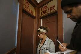 Checking for a potential code violations, Community Organizer with the Central City SRO Collaborative Karin Drucker with tenant organizer JC Castle knock on doors inside the The Ellis Hotel in San Francisco, Calif.