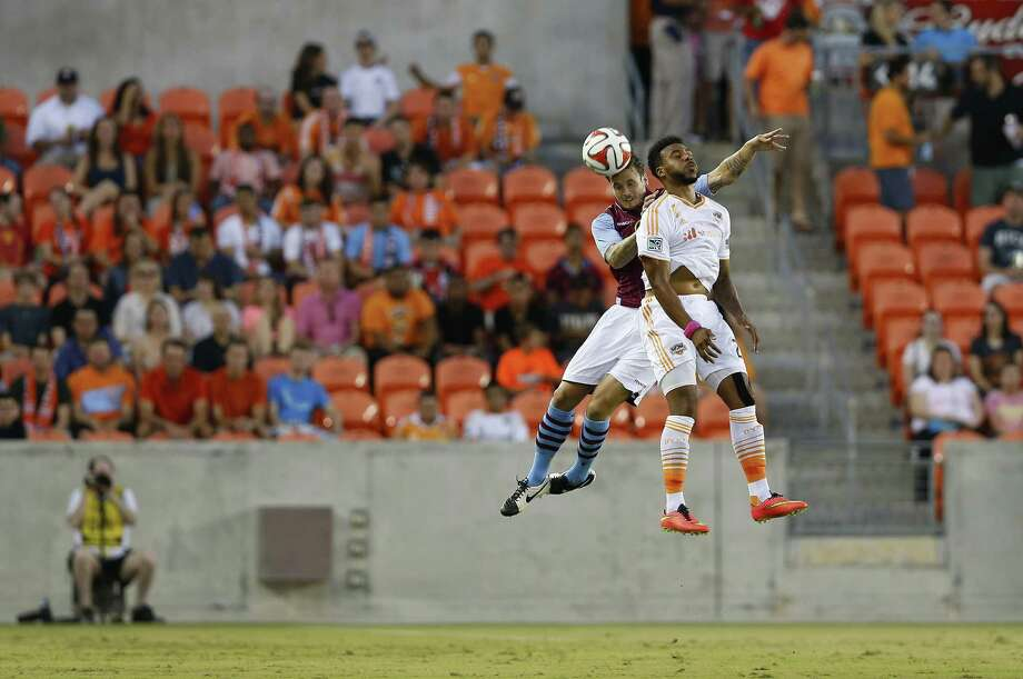 Defender Chris Herd (L) of Aston Villa and forward Giles Barnes (R) of the Houston Dynamo go up for a header during the BBVA Compass Dynamo Charities Cup between Aston Villa and the Houston Dynamo at BBVA Compass Stadium in Houston, Texas on July 26, 2014. AFP PHOTO/Aaron M. SprecherAaron M. Sprecher/AFP/Getty Images Photo: AARON M. SPRECHER, Stringer / AFP