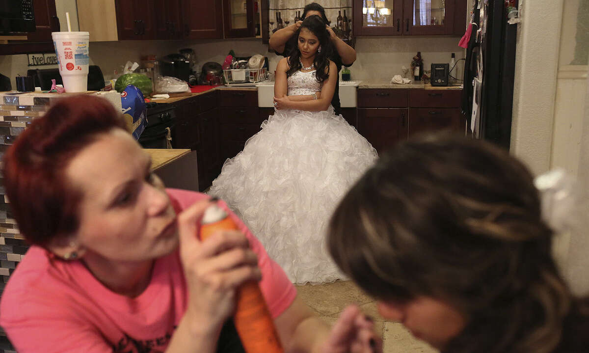 Lisa Rivera (from left), Erica Sandoval (back), Victoria Sandoval and Giselle Maldonado get ready for Victoria's quinceañera at her home on the East Side. Historically African-American, the area now has a Hispanic majority.