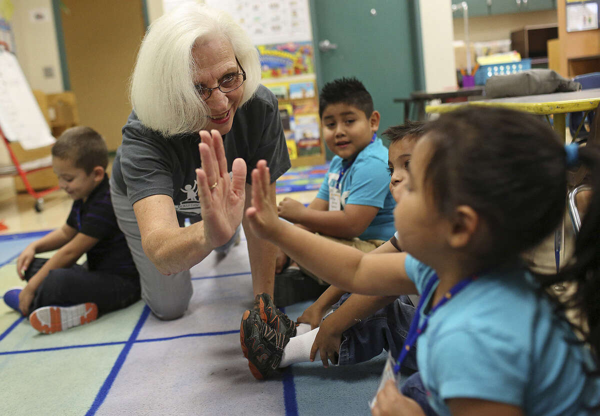 Judy Ratlief of Promise Neighborhood checks on students' first day of Kinder Camp at Pershing Elementary.