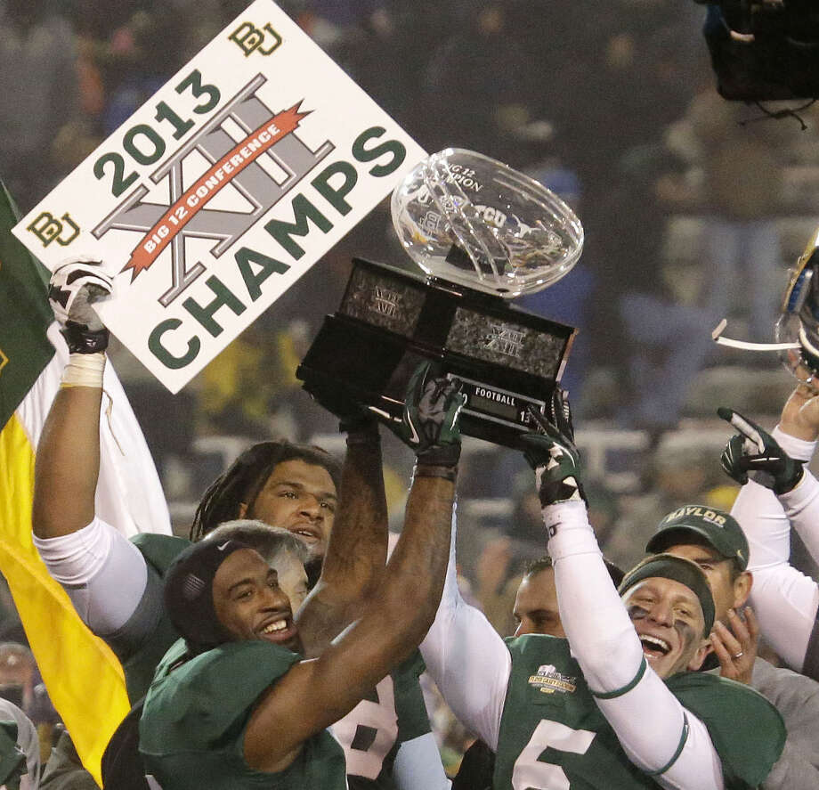 Ahmad Dixon (left) and Eddie Lackey hoist the Big 12 trophy after Baylor beat Texas on Dec. 7 to clinch the league title in its final regular-season game. Baylor was 7-1 in the conference. Photo: L.M. Otero / Associated Press / AP