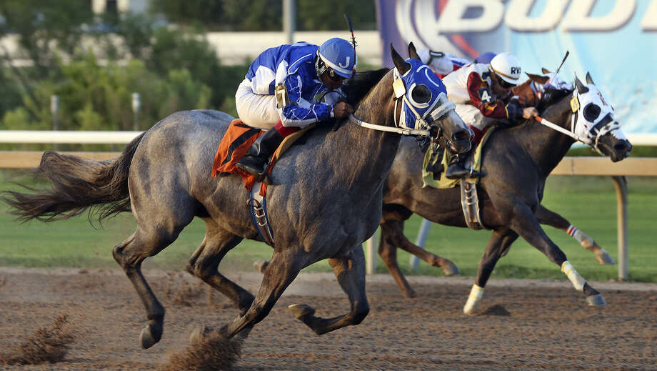Tallulah Moon (7) out sprints Carters Money (4) to win the fourth race in the John Deere Juvenile Challenge with jockey Jose Amador Alvarez aboard at Retama Park on July 26, 2014. Photo: TOM REEL