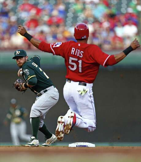 Texas' Alex Rios tries unsuccessfully to break up a double play in the second inning as A's second baseman Eric Sogard prepares to throw to first. Photo: Ron Jenkins / Fort Worth Star-Telegram / Fort Worth Star-Telegram