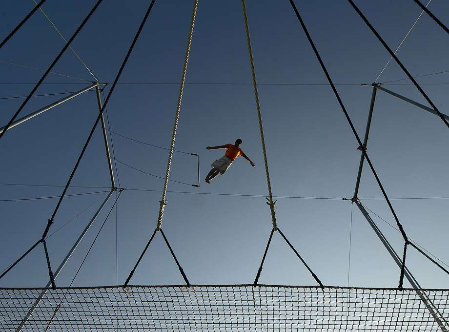 Trapeze artist and instructor Chad Davis of Lone Star Trapeze Academy flies from the swing while practicing before a Brazos Valley Bombers Texas Collegiate League baseball game at Cellucor Field in Bryan, Texas Friday, July 25, 2014.  The trapeze is set up along the right field line at the ball park, allowing spectators to view the action. (AP Photo/Bryan-College Station Eagle, Stuart Villanueva) Photo: Stuart Villanueva/ The Eagle, Associated Press