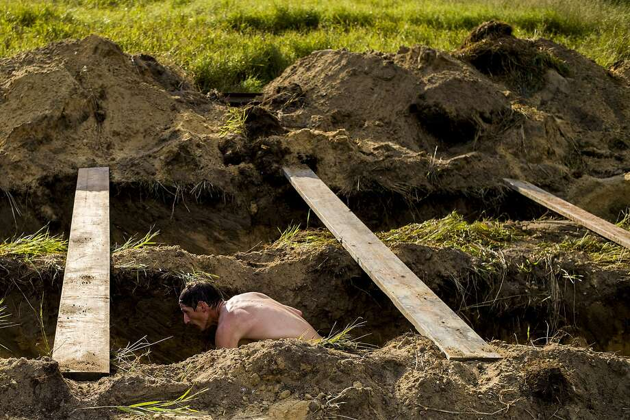 "A man crouches under slates of wood as he burrows through the ""Trenches"" obstacle in the first heat of runners during the fourth annual Michigan Warrior Dash on Saturday, July 26, 2014, at the E.A. Cummings Center near Mount Morris, Mich. (AP Photo/The Flint Journal, Jake May) LOCAL TELEVISION OUT; LOCAL INTERNET OUT Photo: Jake May, Associated Press"