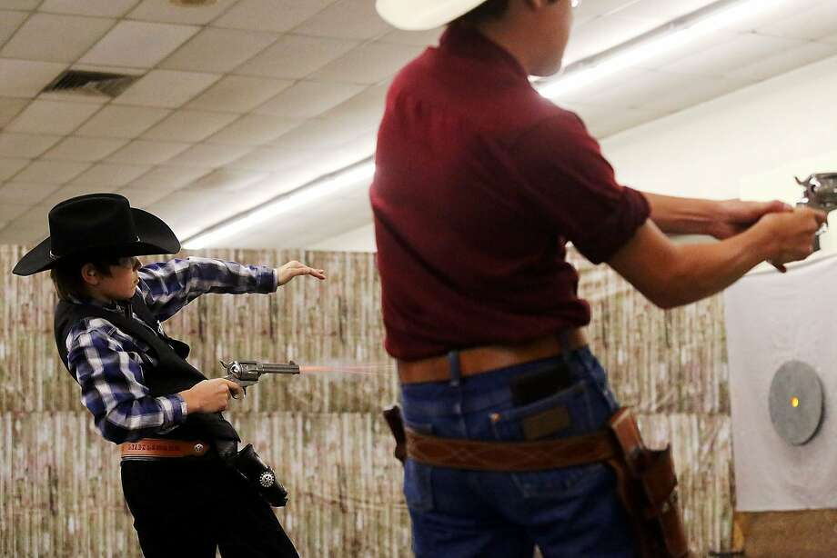 Thirteen-year-old Coby 'Lone Star Lead Slinger' Williams, left, competes in the Billy The Kid age group during the Cowboy Fast Draw Association Southern Territorial Championship Saturday July 26, 2014 at Barn G at the Ector County Coliseum in Odessa, Texas. (AP Photo/Odessa American, Edyta Blaszczyk) Photo: Edyta Blaszczyk|Odessa American, Associated Press