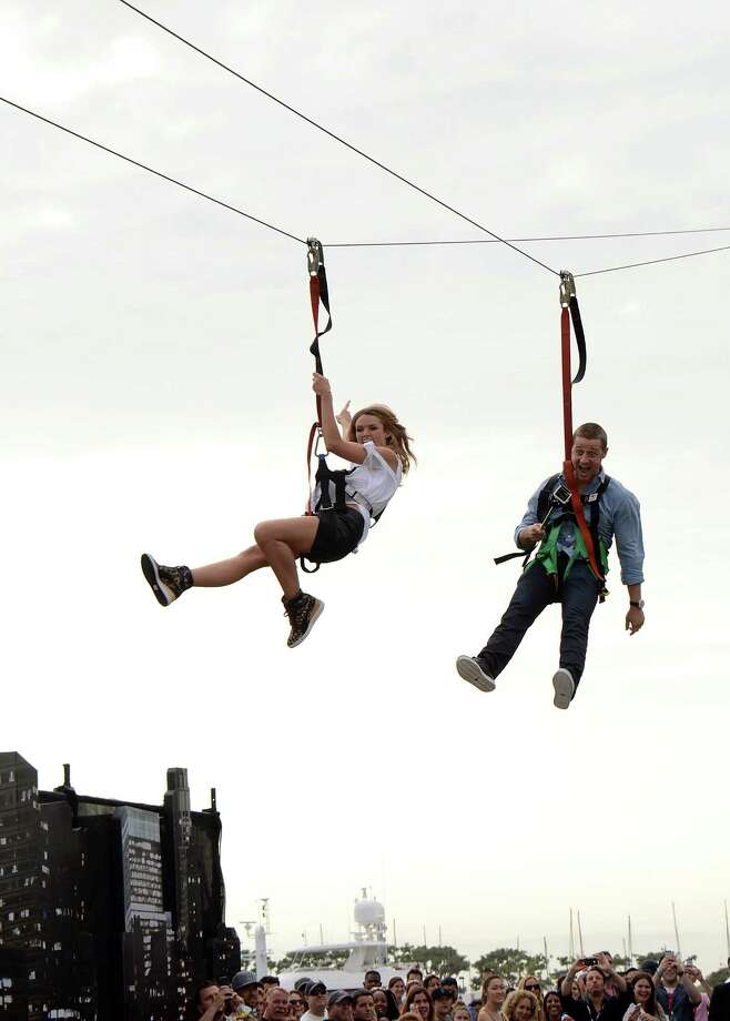 """Erin Richards, left, and Benjamin McKenzie zipline at the """"Gotham"""" press line on Day 3 of Comic-Con International on Saturday, July 26, 2014, in San Diego. (Photo by Tonya Wise/Invision/AP) Photo: Tonya Wise, Tonya Wise /Invision/AP / AP2014"""