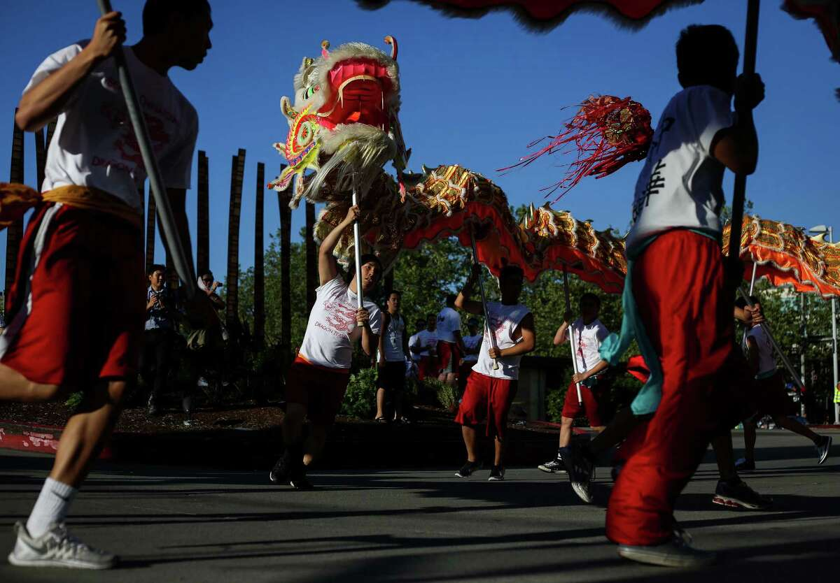 The 100-foot dragon weaves through a parking lot prior to the Alaska Airlines Seafair Torchlight Parade on Saturday, July 26, 2014. Thousands lined the streets to watch the parade which featured drill teams, marching bands, pirates, floats, and Sounders players Clint Dempsey and DeAndre Yedlin.