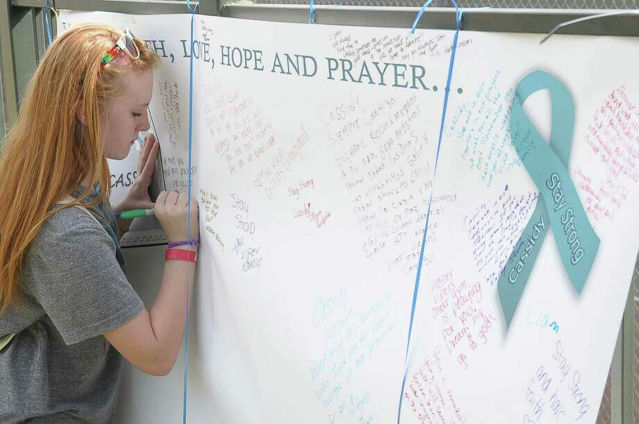 Abby Murray (13) leaves a message of condolance during the Stay Family Celebration of Life fund-raiser at Forest Oaks Swim and Racquet Club in Spring Saturday July 26, 2014. Six members of the Stay family were shot to death in their Spring home on July 9. Photo: Copyright Tony Bullard 2014, Tony Bullard / Copyright 2014 Tony Bullard & the Houston Chronicle