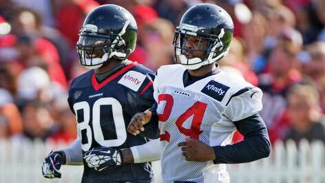Houston Texans wide receiver Andre Johnson (80) and  cornerback Johnathan Joseph (24) run alongside each other during a pass coverage drill during Texans training camp at the Methodist Training Center Sunday, July 27, 2014, in Houston.