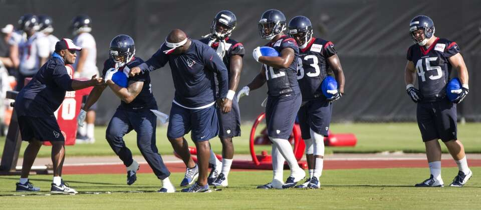 Day 2: July 27  Running back Arian Foster, left, runs a drill.
