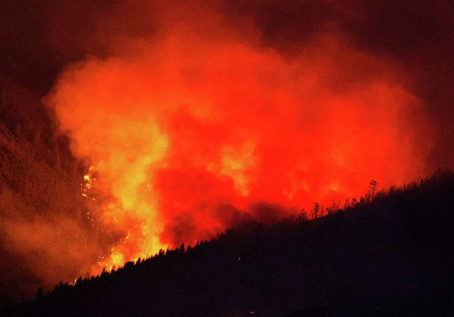 In this July 24, 2014 photo, a wildfire burns in the mountains above Levan, Utah. Authorities say the blaze flared late Thursday afternoon on the south side of the Juab County community. Photo: Steve Griffin, AP  / 2014 Steve Griffin