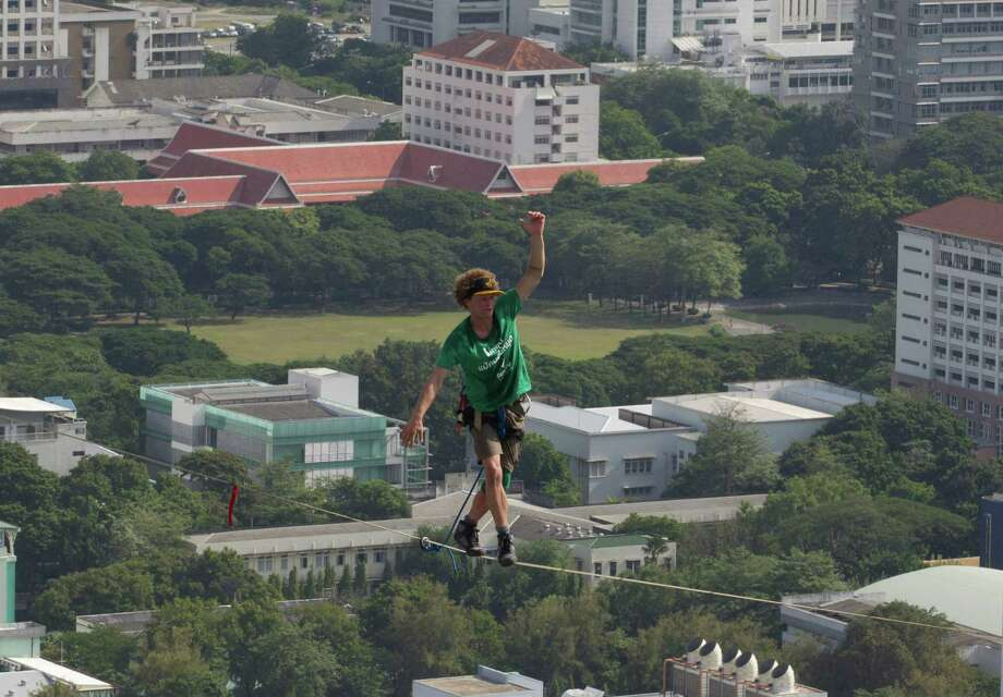 U.S. slackliner Andy Lewis of Calif. balances on a 169 meters (555 feet)-long slackline in Bangkok, Thailand Wednesday, July 23, 2014. Lewis' balancing act was to promote a consumer product. Photo: Sakchai Lalit, AP  / AP
