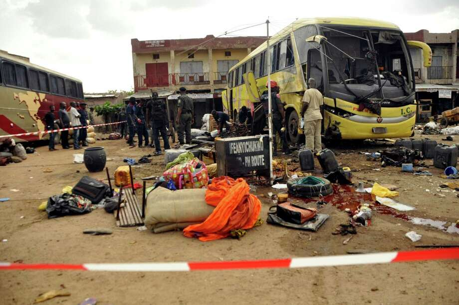 "Police officers inspect a passenger bus following an explosion at a bus station in Kano, Nigeria. Thursday July 24, 2014. According to police, one person was killed and eight others injured after a bomb exploded out of a discarded refrigerator at the bus station. Kano State Police Commissioner Aderenle Shinaba said ""the investigation into the terrorism is ongoing."" Photo: Muhammed Giginyu, AP  / AP2014"