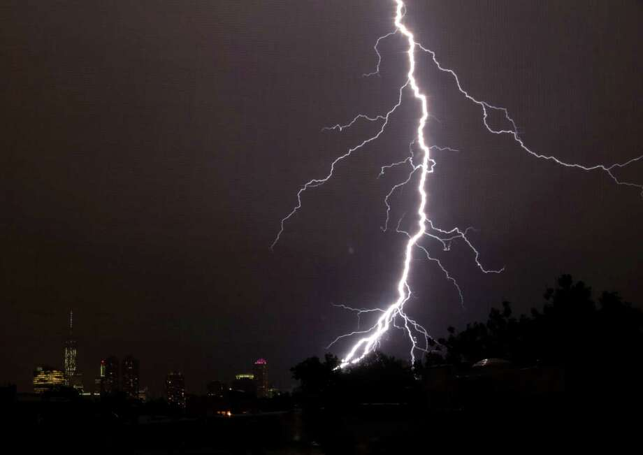 A lightning bolt strikes down during a storm with the One World Trade Center tower, left, as a backdrop, Wednesday, July 23, 2014, in Jersey City, N.J. Photo: Julio Cortez, AP  / AP2014