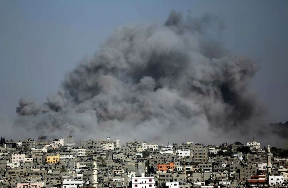 Smoke from an Israeli strike rises over the Gaza Strip, Friday, July 25, 2014. Israeli warplanes struck houses throughout the Gaza Strip as international efforts continue to broker a cease fire in the 18 day-old war. Photo: Hatem Moussa, AP  / AP2014