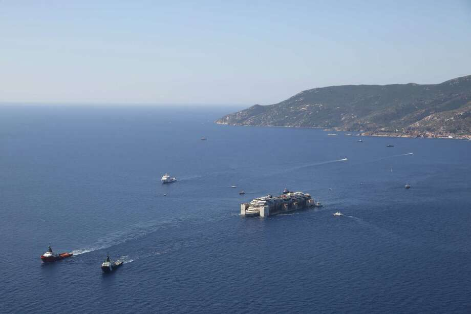 In this aerial picture provided by the Italian Civil Protection Department, the wreck of the Costa Concordia is towed by two tugboats as it leaves behind the tiny Tuscan island of Isola del Giglio,  Italy, Wednesday, July 23, 2014. The Costa Concordia cruise liner has begun its final voyage away from the tiny Italian island where it capsized on Jan. 13, 2012, killing 32 people. Photo: AP  / AP2014