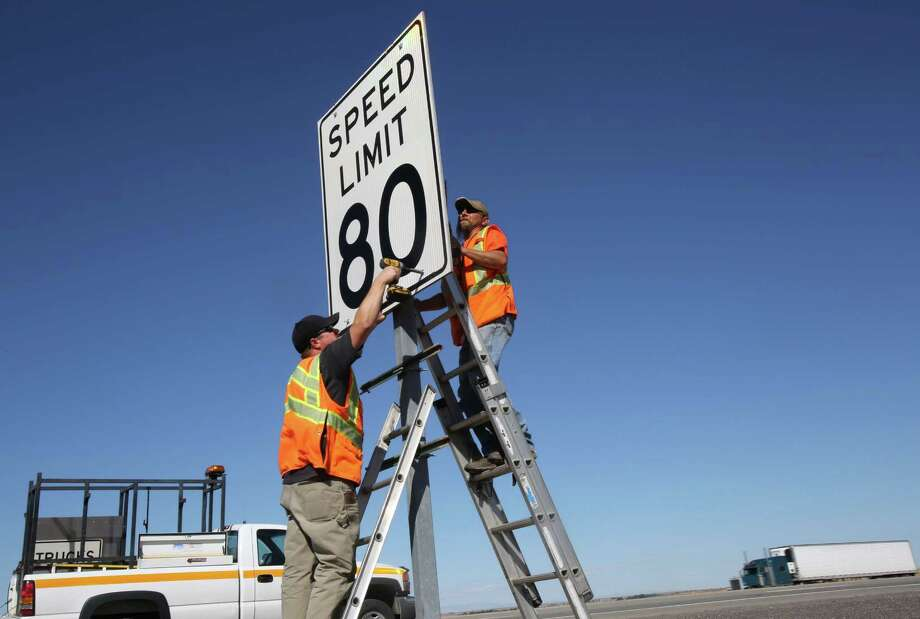 Kevin Daughdrill, left, and Eric Allen, of the Idaho Transportation Department, place a new speed limit sign along the westbound lanes of Interstate 84 east of Mountain Home, Idaho, Thursday, July 24, 2014. Photo: Joe Jaszewski, AP  / Idaho Statesman