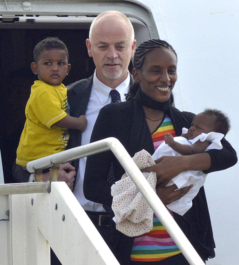 "Meriam Ibrahim, from Sudan, holds her baby girl Maya, accompanied by Italian deputy Foreign Minister Lapo Pistelli, holding her son Martin, after landing from Khartoum, at Ciampino's military airport, on the outskirts of Rome, Thursday, July 24, 2014. Meriam Ibrahim, the Sudanese woman who was sentenced to death in Sudan for refusing to recant her Christian faith has arrived in Italy along with her family, including an infant born in prison. Italy's premier welcomed Meriam Ibrahim at Rome's Ciampino airport on Thursday, calling it ""a day of celebration."" Ibrahim, whose father was Muslim but whose mother was an Orthodox Christian from Ethiopia, was accompanied by her husband, who is a citizen of both the United States and South Sudan, her 18-month-old son and an infant born May 27. The family is to spend a few days in Rome before heading to the United States. Photo: Daniele Leone, AP  / PRESL"