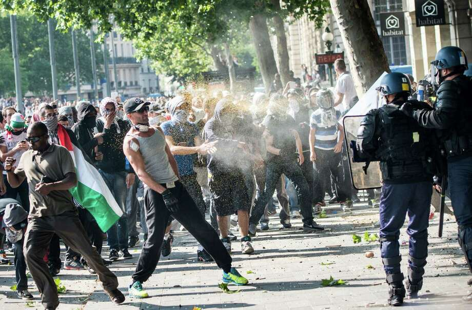 A riot police officer sprays pro-Palestinian protesters as clashes erupted during a banned demonstration in support of Gaza at Place de la Republique in Paris, France, Saturday, July 26, 2014. French police fired tear gas as clashes broke out at a banned pro-Gaza demonstration on Saturday as thousands defied a ban on the protest. The interior minister had earlier called on organizers of the Paris demonstration to observe the ban imposed to halt potential anti-Semitic violence. Photo: Benjamin Girette, AP  / AP