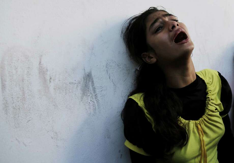 A displaced Palestinian girl who had lost her relative in an Israeli airstrike at a U.N school cries at Beit Hanoun hospital in the northern Gaza Strip, Thursday, July 24, 2014. Israeli tank shells hit a compound housing a U.N. school in the Gaza Strip on Thursday, killing more than a dozen of people and wounding dozens who were seeking shelter from fierce clashes on the streets outside, Palestinian officials said, as Israel pressed forward with its 17-day war against the territory's Hamas rulers. Photo: Adel Hana, AP  / THE ASSOCIATED PRESS2014