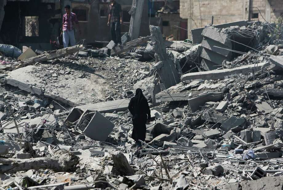 Palestinians walk by the rubble of houses destroyed by Israeli strikes in Beit Hanoun, northern Gaza Strip, Saturday, July 26, 2014. Thousands of Gaza residents who had fled Israel-Hamas fighting streamed back to devastated border areas during a lull Saturday, and were met by large-scale destruction: scores of homes were pulverized, wreckage blocked roads and power cables dangled in the streets. Photo: Lefteris Pitarakis, AP  / AP2014