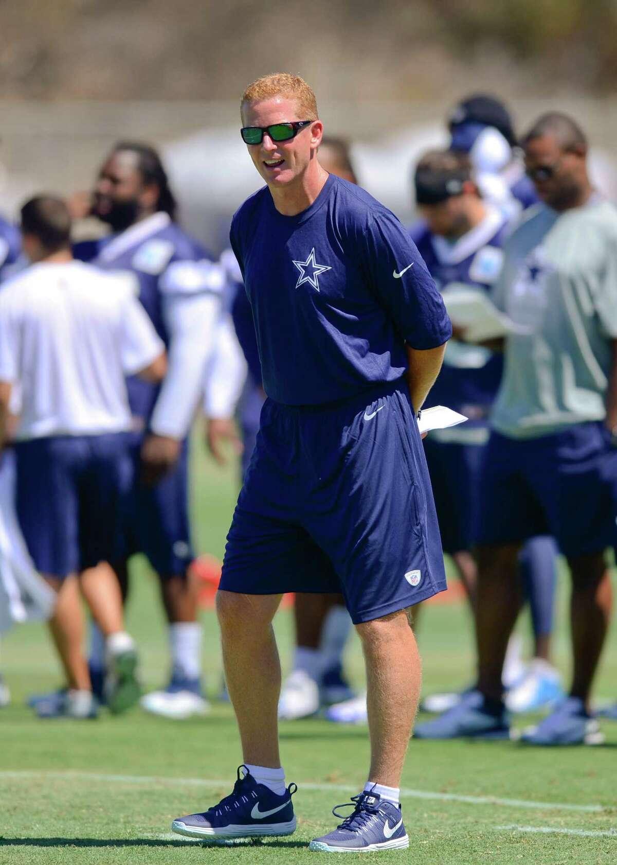 Dallas Cowboys head coach Jason Garrett yells out instructions as they run the offense during NFL football training camp, Thursday, July 24, 2014, in Oxnard, Calif. (AP Photo/Gus Ruelas)