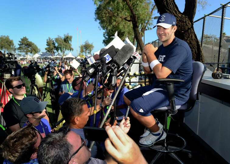 Dallas Cowboys quarterback Tony Romo, right, gives a news conference about his recovery from back su