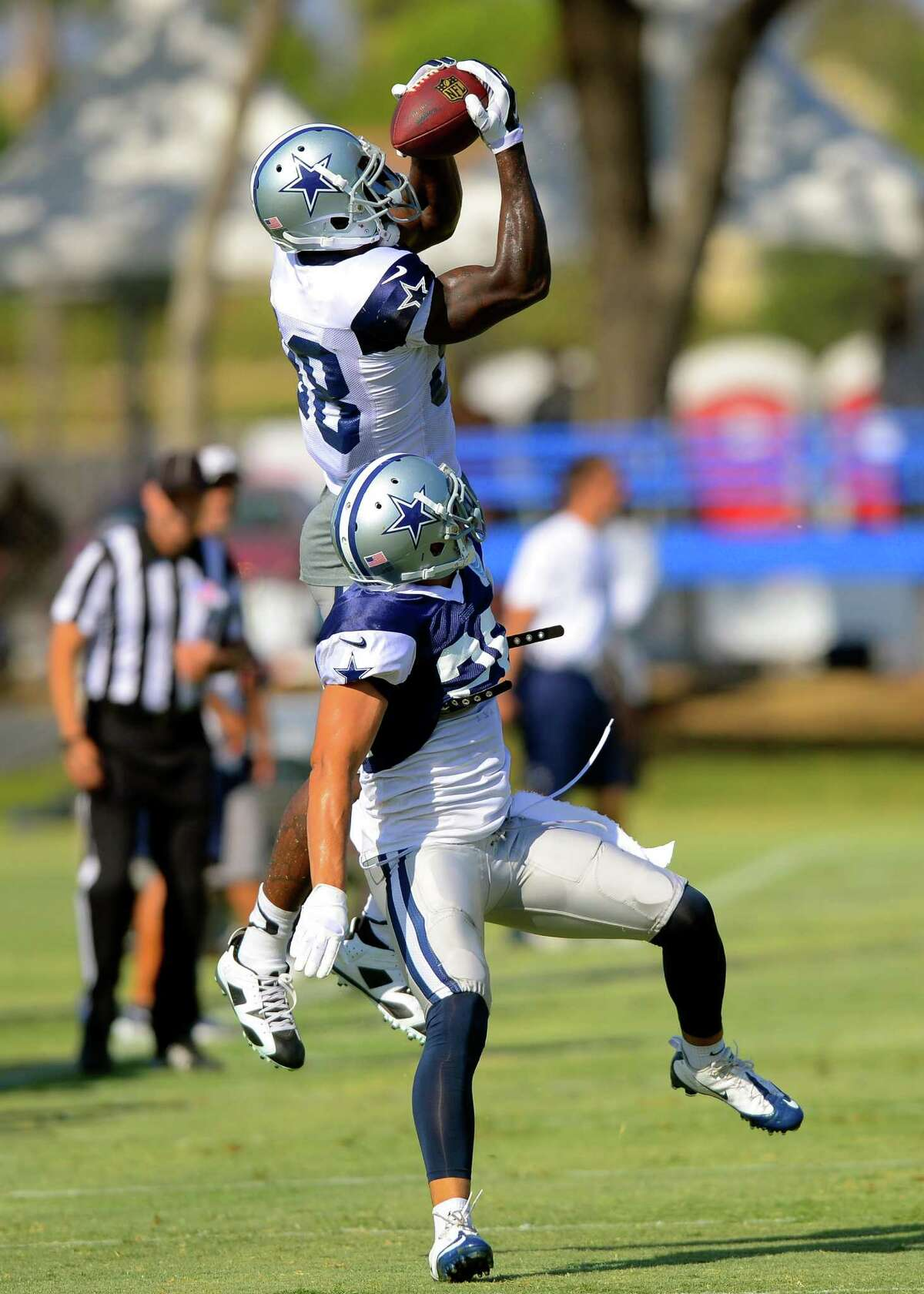 Dallas Cowboys cornerback Sterling Moore, front bottom, attempts to break up a pass to wide receiver Dez Bryant, back top, at NFL training camp, Saturday, July 26, 2014, in Oxnard, Calif. (AP Photo/Gus Ruelas)