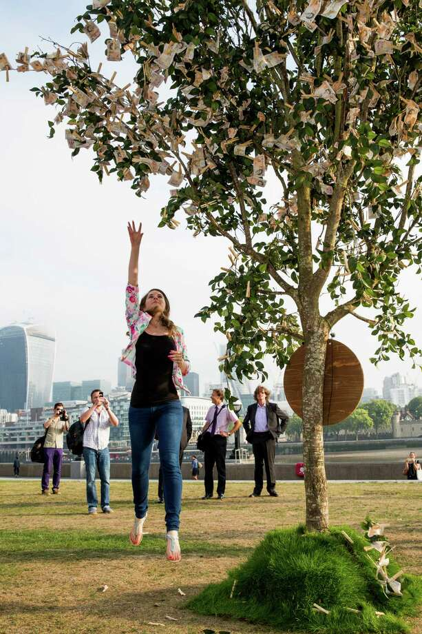 Londoners walking through Potters Field Park were surprised to see a 'money tree'  blooming with £9820 in £10 notes, the average amount a working British family has in savings, on July 24, 2014 in London, England. The tree was planted by Sunlife to encourage the nation to start saving at least £10 a month for a brighter future. Photo: Tristan Fewings, Getty Images / 2014 Getty Images