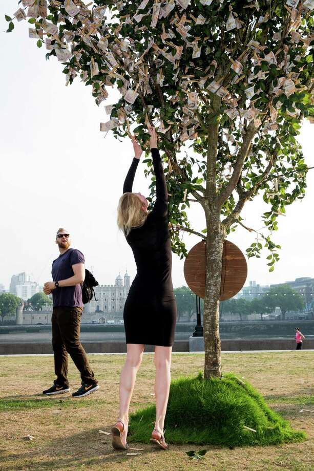 Londoners walking through Potters Field Park were surprised to see a 'money tree'  blooming with the average amount a working British family has in savings, on July 24, 2014 in London, England. The tree was planted by Sunlife to encourage the nation to start saving at least 10 pounds a month for a brighter future. Photo: Tristan Fewings, Getty Images / 2014 Getty Images