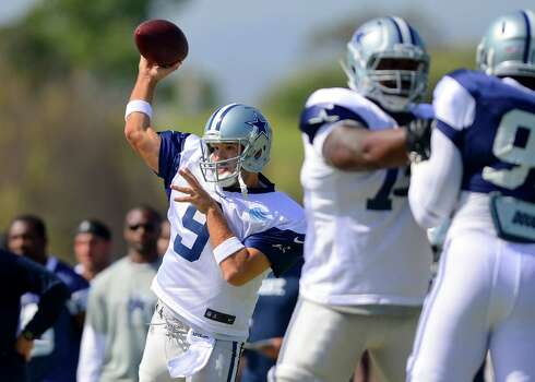 Dallas Cowboys quarterback Tony Romo (9) throws a pass as the offense runs a play during NFL training camp on Saturday, July 26, 2014, in Oxnard, Calif. (AP Photo/Gus Ruelas) Photo: Gus Ruelas, Associated Press / FR157633 AP