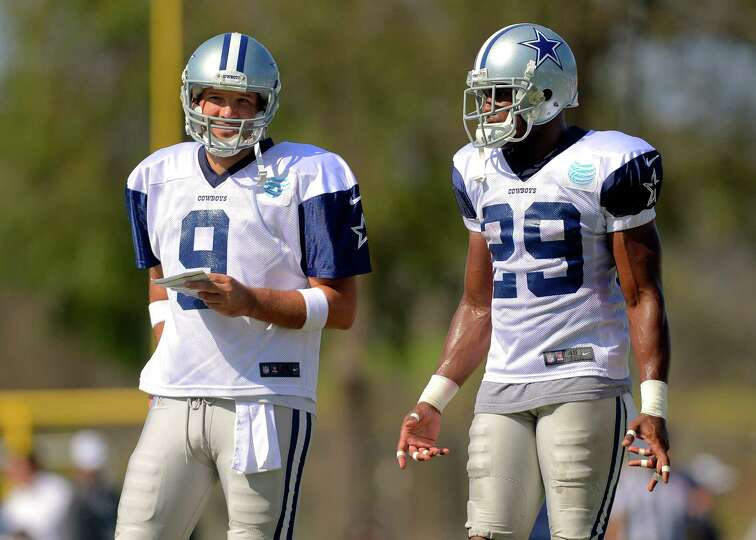 Dallas Cowboys quarterback Tony Romo (9) and teammate running back DeMarco Murray (29) talk things o