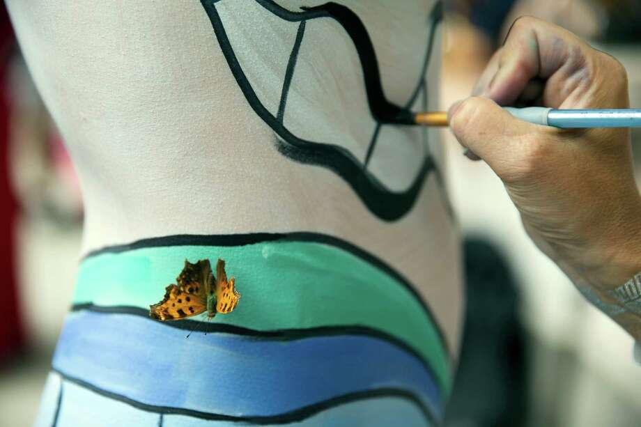 A moth lands on a model as she is painted at Columbus Circle as part of an event featuring artist Andy Golub, Saturday, July 26, 2014, in New York. Golub says New York was the only city in the country that would allow his inaugural Bodypainting Day. Photo: John Minchillo, AP  / FR170537 AP