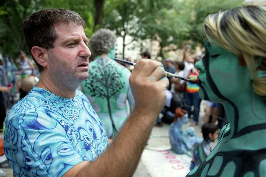 Artist Andy Golub paints a model at Columbus Circle as body-painting artists gathered to decorate nude models as part of an event lead by Golub, Saturday, July 26, 2014, in New York. Golub says New York was the only city in the country that would allow his inaugural Bodypainting Day. Photo: John Minchillo, AP  / FR170537 AP