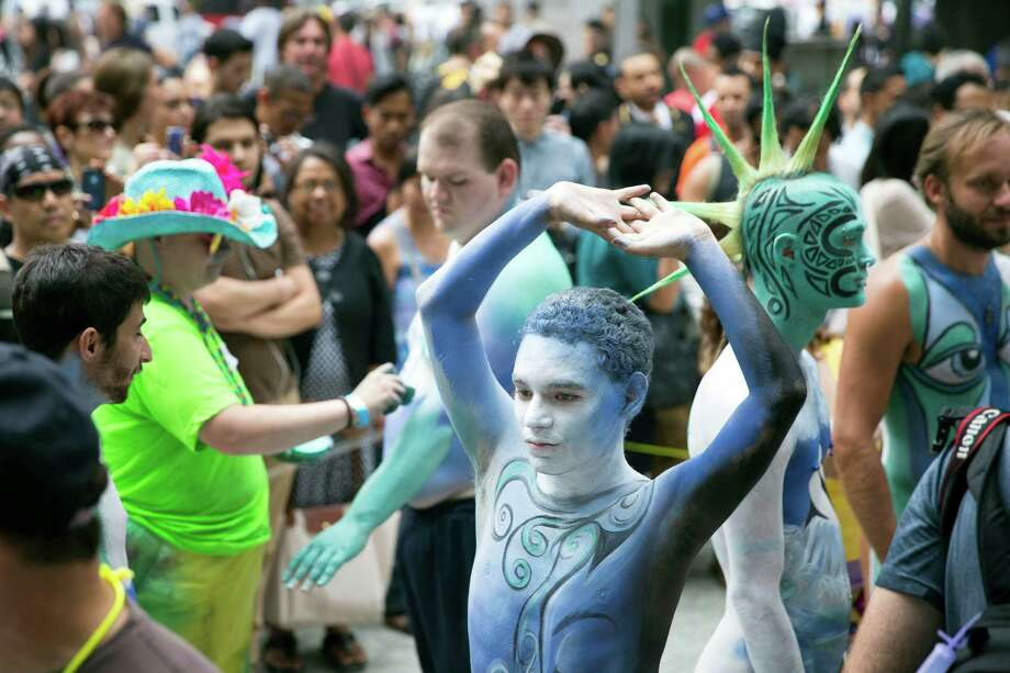 Crist Crow stretches after being painted at Columbus Circle as body-painting artists gathered to decorate nude models as part of an event featuring artist Andy Golub, Saturday, July 26, 2014, in New York. Golub's event Saturday included a post-painting march down Broadway and a return to Times Square for a photo shoot. Photo: John Minchillo, AP  / FR170537 AP