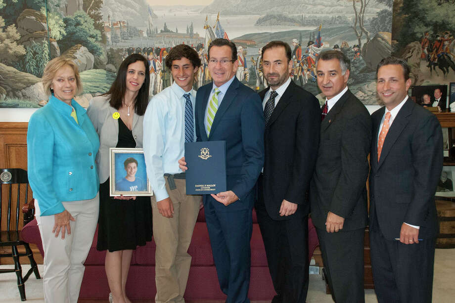 State Sens. Bob Duff right, and Carlo Leone, second from right, joined Gov. Dannel P. Malloy, center, and state Rep. Terrie Wood, R-Darien, left, for a signing ceremony to commemorate the passage of new legislation that will promote greater awareness of sudden cardiac arrest. They were joined by the family members of Andy Pena, a Darien student-athlete who died from the condition in 2011. Photo: Contributed Photo, Contributed / Darien News