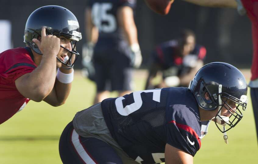 Day 2: July 27  Quarterback Tom Savage, left, lines up to take a sn