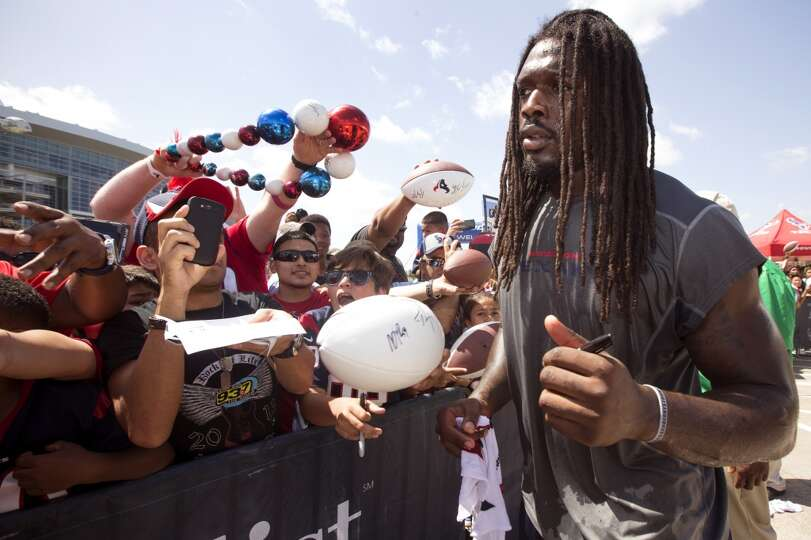 Day 2: July 27  Linebacker Jadeveon Clowney, right, signs autograph