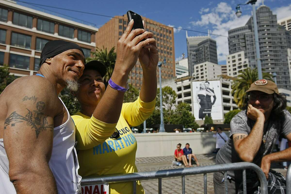Ronnie Goodman takes a photo with Darice Caudle after finishing the San Francisco Marathon on Sunday, July 27, 2014 in San Francisco, Calif. Goodman is a homeless artist who lives in a tent under the freeway who has long dreamed of running in the marathon.