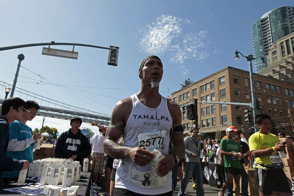 Ronnie Goodman gets a box of water after crossing the finish line of the San Francisco Marathon on Sunday, July 27, 2014 in San Francisco, Calif. Goodman is a homeless artist who lives in a tent under the freeway who has long dreamed of running in the marathon.