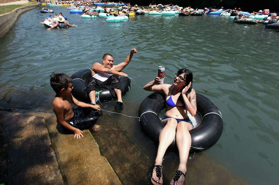 """Anna Malek (front) holds onto to her canned drink while tubing the Comal River with Ayden Gomez and his son, Ayden Gomez, Jr., near Hinman Island Park in New Braunfels on Saturday, July 26, 2014. The 2012 """"can ban"""" ordinance was ruled unconstitutional by State District Court Judge Don Burgess in January. Patrons tubing on the river, for now, can bring cans of beverages without breaking any laws while the city of New Braunfels appeals the ruling. Photo: Kin Man Hui, San Antonio Express-News / ©2014 San Antonio Express-News"""