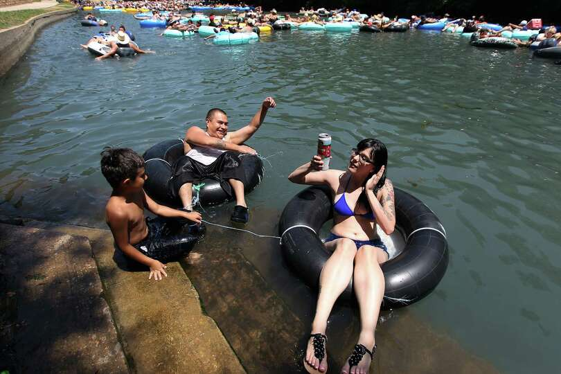 Anna Malek (front) holds onto to her canned drink while tubing the Comal River with Ayden Gomez and