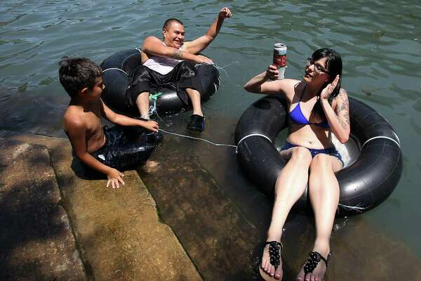 "Anna Malek (front) holds onto to her canned drink while tubing the Comal River with Ayden Gomez and his son, Ayden Gomez, Jr., near Hinman Island Park in New Braunfels on Saturday, July 26, 2014. The 2012 ""can ban"" ordinance was ruled unconstitutional by State District Court Judge Don Burgess in January. Patrons tubing on the river, for now, can bring cans of beverages without breaking any laws while the city of New Braunfels appeals the ruling."